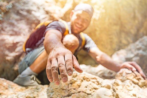 Photo d'un homme tendant la main pour aider à grimper un rocher. Sophrologie, Hypnose, Synergie sur Marseille