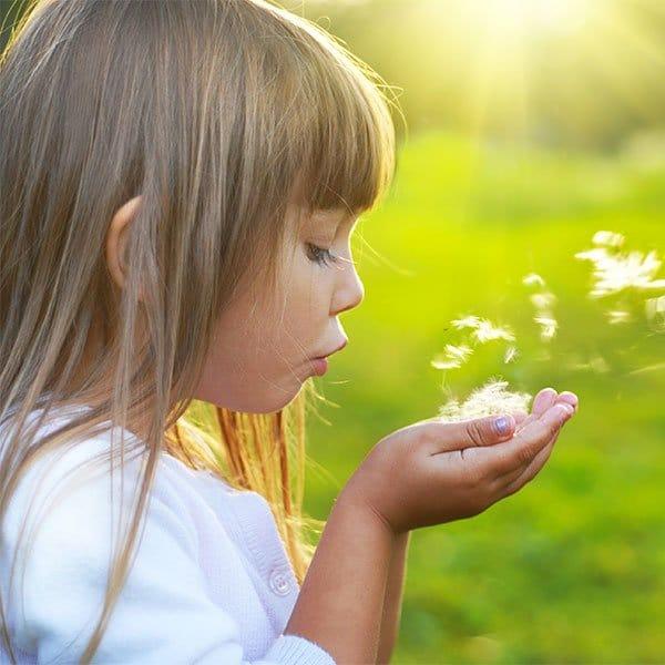 Photo d'une petite fille qui souffle sur des fleurs. Sophrologie, Hypnose, Synergie sur Marseille