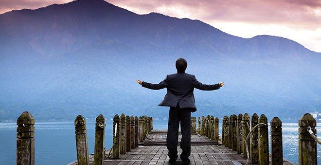 Photo d'une homme d'affaire regardant un paysage les bras ouvert, symbole de bien-être. Sophrologie, Hypnose, Synergie sur Marseille