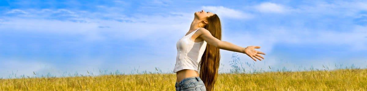 Photo d'une femme sous le soleil dans un champ de blé. Sophrologie, Hypnose, Synergie sur Marseille