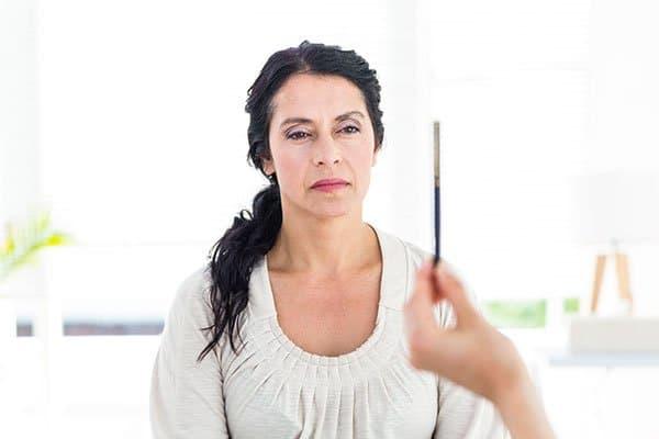 Photo d'une femme lors d'une séance de mouvements alternatifs, suivant du regard un stylo. Sophrologie, Hypnose, Synergie sur Marseille