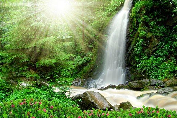 Photo d'une cascade sous un grand soleil. Sophrologie, Hypnose, Synergie sur Marseille